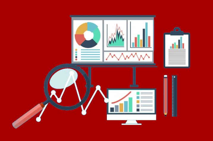 digital marketing graphs on various devices and a magnifying glass